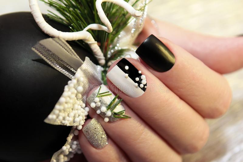 Christmas black and white manicure. With silver balls and Christmas ornament on female hand close up stock photography