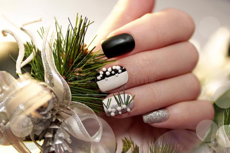 Christmas black and white manicure. With silver balls and Christmas ornament on female hand close up stock photo