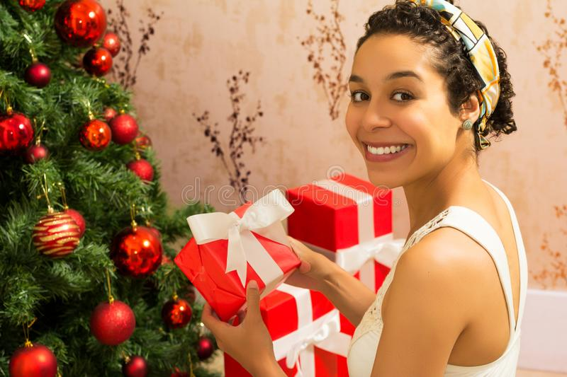 Christmas. Black woman is holding red gift box. Christmas tree. Christmas. Black woman with short curtly hair is showing gift box. Christmas tree with red stock image
