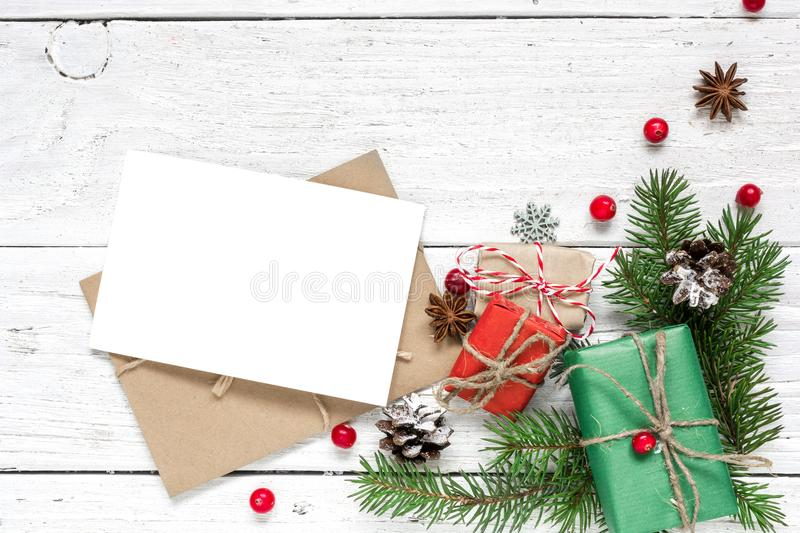 Christmas blank greeting card and envelope with fir tree branches, red berries, pine cones and gift boxes stock images