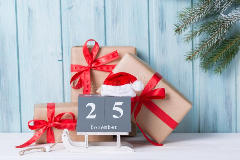 Christmas block calendar with 25 December and gift boxes, wooden background with fir tree branch stock image