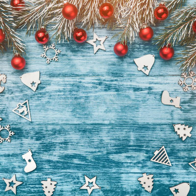 Christmas blue background with decoration, red baubles, wooden ornamented toys and fir tree branch. Copy space, top view royalty free stock photography