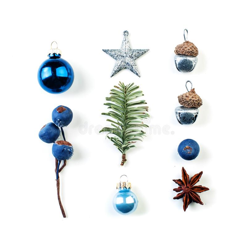 Christmas blue decorations. Rows of blue berries, silver star, baubles and green fir branch on white background royalty free stock photos