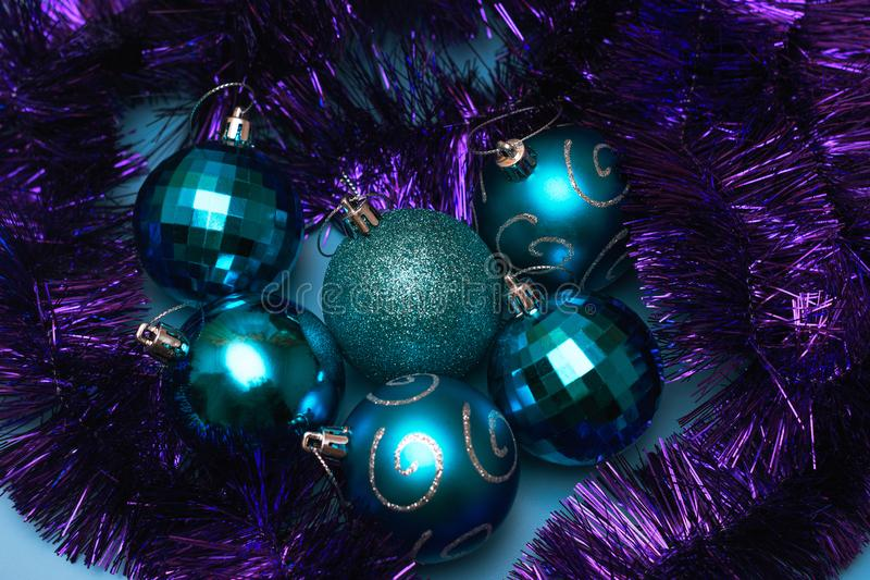 Christmas blue toys lie surrounded by festive purple tinsel, top view. Tree, glamorous, holiday, background, decoration, shiny, orange, winter, year stock photography