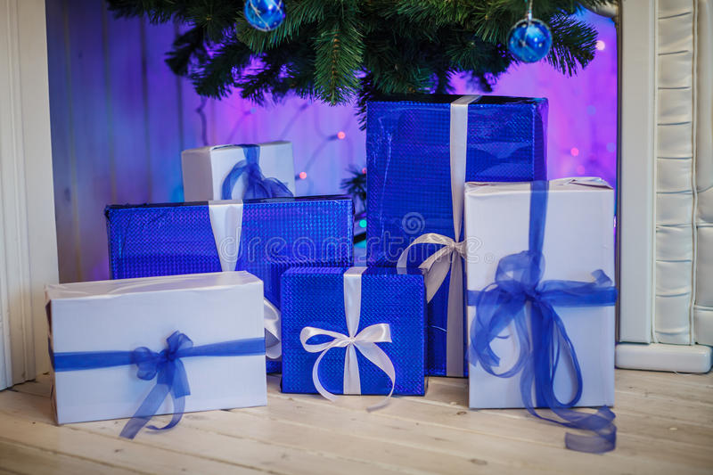 Christmas blue and white boxes under the tree. New year gifts. royalty free stock images