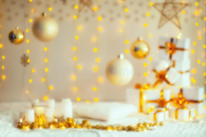 Christmas blurred decorating composition. Christmas gifts with gold ribbon, pillow, knitted blanket, christmas balls and stars stock photography