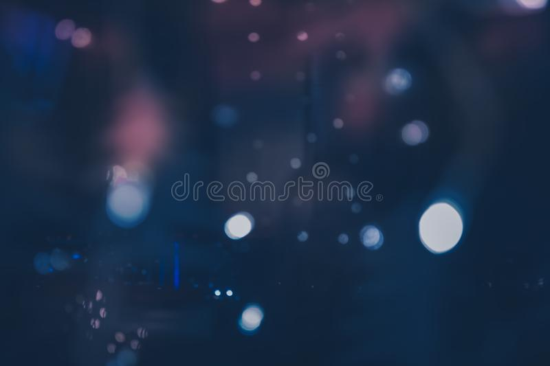 Christmas bokeh night background vintage New year with defocused Christmas lights black blue pink lilac colors stock photo