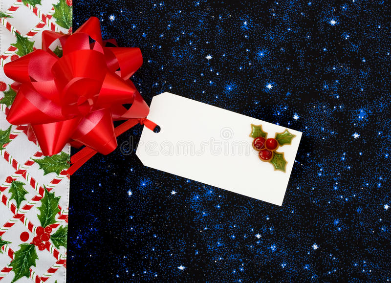 Christmas Border. A border of candy canes and holly berries with leaves on a blue background, Christmas border royalty free stock image