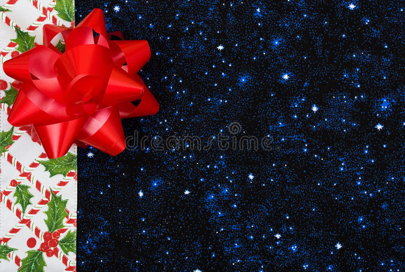 Christmas Border. A border of candy canes and holly berries with leaves on a blue background, Christmas border royalty free stock photography