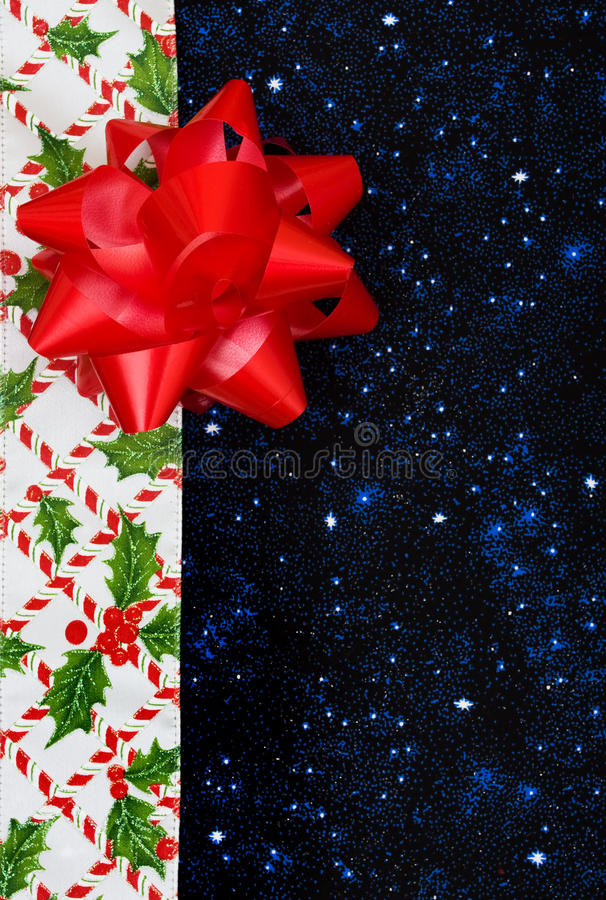 Christmas Border. A border of candy canes and holly berries with leaves on a blue background, Christmas border stock photography