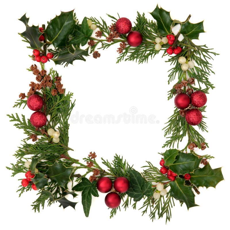 Christmas Border. Christmas decorative border of holly, ivy, mistletoe, cedar leaf sprigs with pine cones and red baubles over white background stock photography