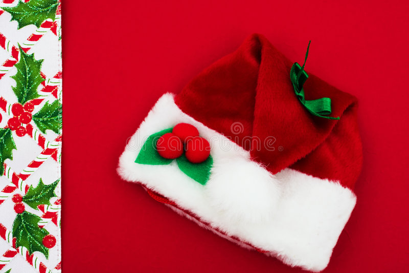 Christmas Border. Candy cane, holly berries and leaf border with Santa hat on red background, Christmas border royalty free stock photo