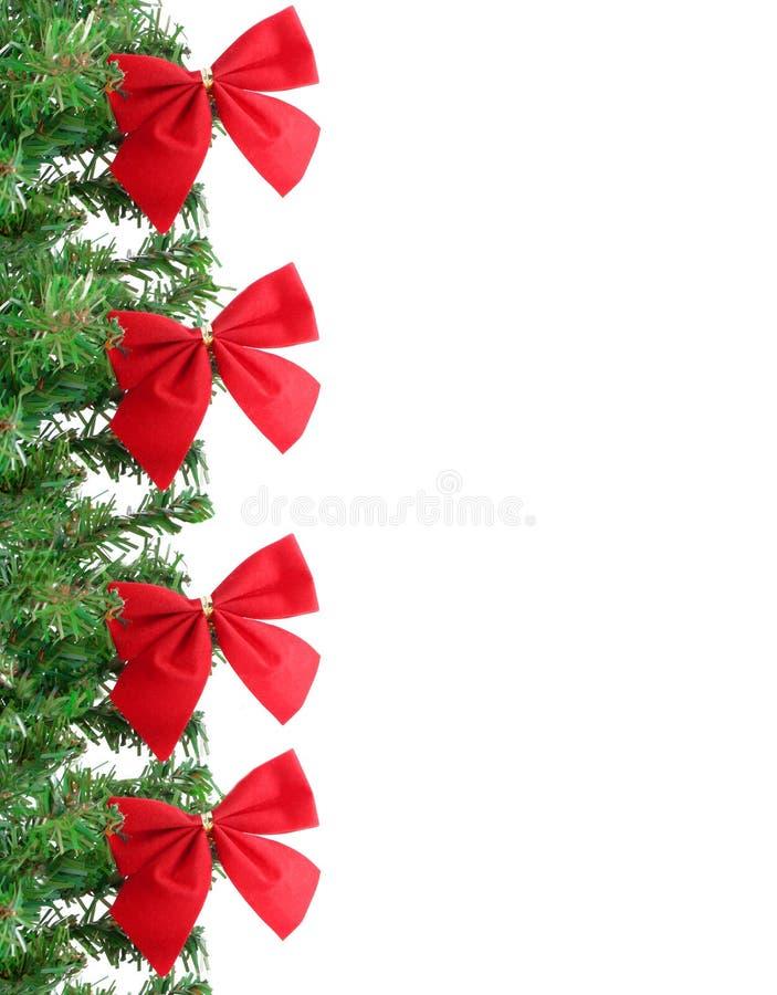 Christmas border. Fake pine tree christmas border with red festive bows royalty free stock image