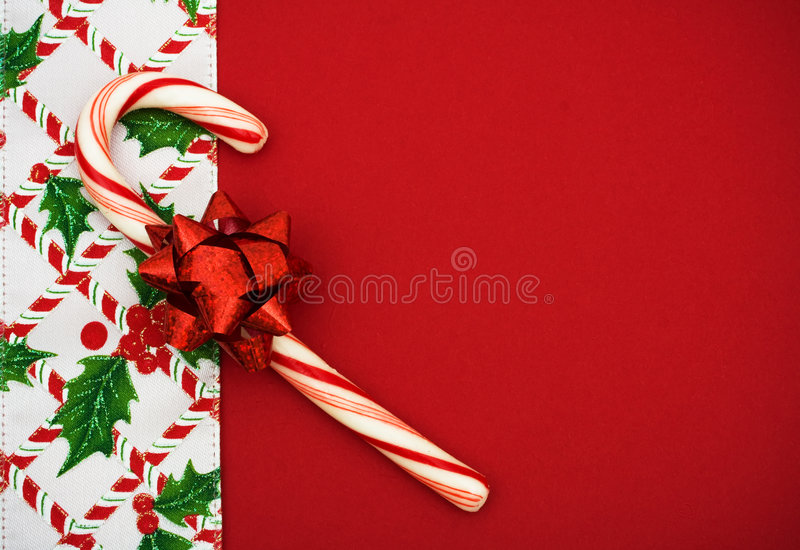Christmas Border. Candy cane, holly berries and leaf border on red background, Christmas border stock photo