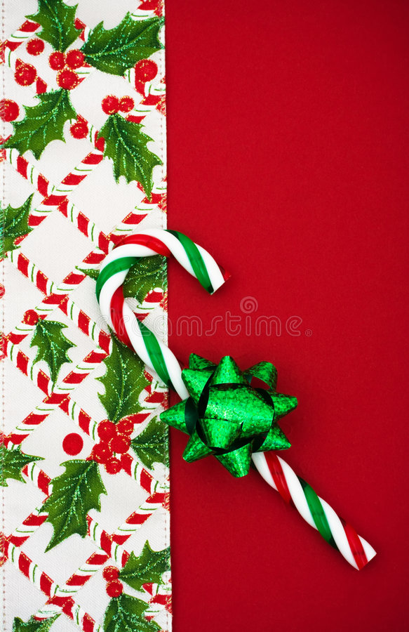 Christmas Border. Green bow and candy cane with holly berries and leaf border on red background, Christmas border royalty free stock photography