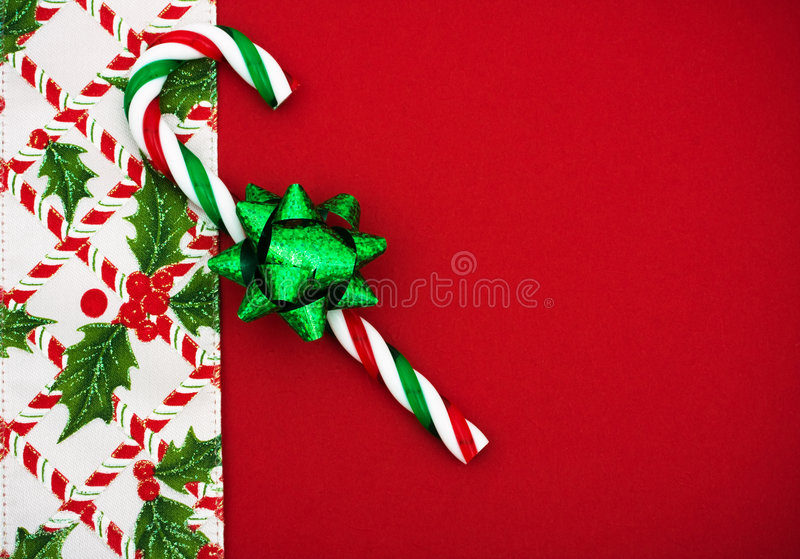 Christmas Border. Green bow and candy cane with holly berries and leaf border on red background, Christmas border stock image