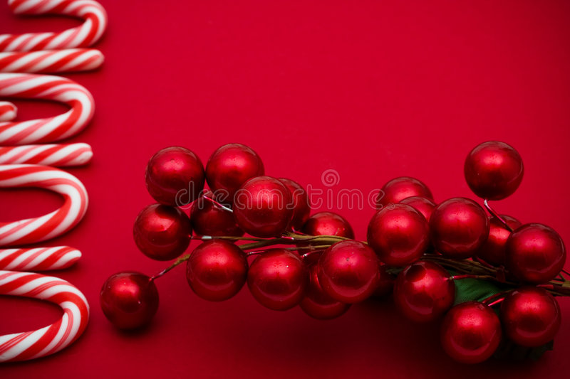 Christmas Border. Candy cane and red berry border on red background, Christmas border royalty free stock photo