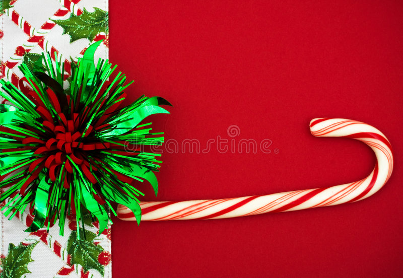 Christmas Border. Green and Red bow and candy cane with holly berries and leaf border on red background, Christmas border royalty free stock photos