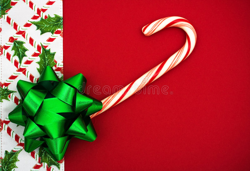 Christmas Border. Red bow and candy cane with holly berries and leaf border on red background, Christmas border stock image