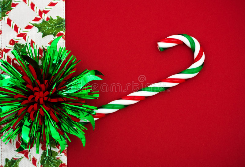 Christmas Border. Green and Red bow and candy cane with holly berries and leaf border on red background, Christmas border stock photo