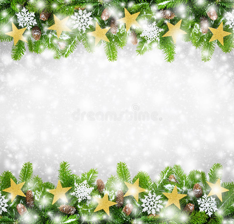 Christmas border background. Christmas border of fir twigs decorated with stars, snow and cones on light gray background with falling snowflakes royalty free stock photo