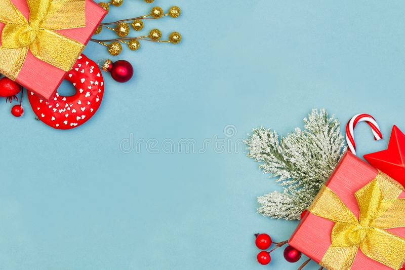 Christmas border background. Red gifts, holly berries and green fir branch on blue background with copy space.  stock photo