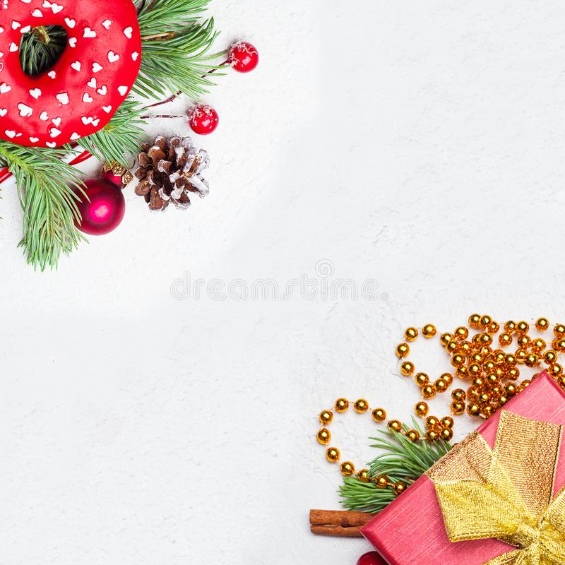 Christmas border background. Xmas composition with green Xmas fir branch, red holly berries, gift and baubles on white royalty free stock photo