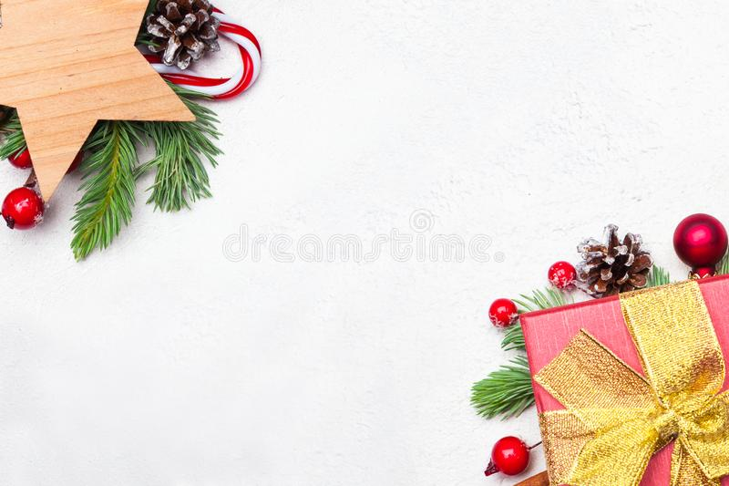 Christmas border background with Xmas decorations. Colorful composition with green Xmas fir branch, gift, stars, red holly berries. And baubles on white royalty free stock images