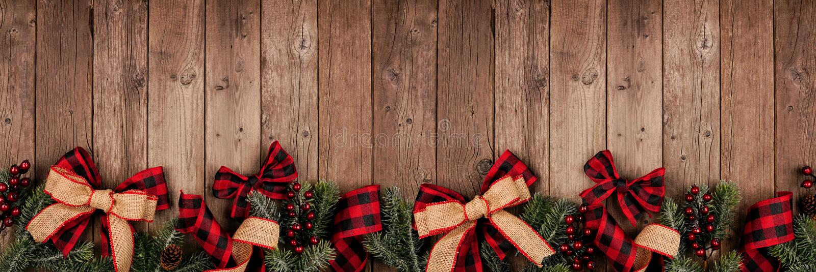christmas border banner red black checked buffalo plaid ribbon burlap tree branches above view rustic wood 163888985