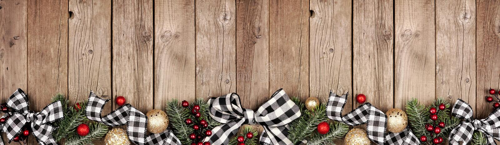 christmas border banner white black checked buffalo plaid ribbon ornaments tree branches above view rustic wood 163888194