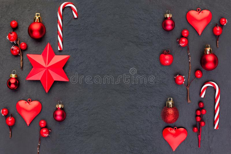 Christmas border on black background. Red Christmas composition with red New Year decor. Flat lay top view on dark background. With copy space royalty free stock images