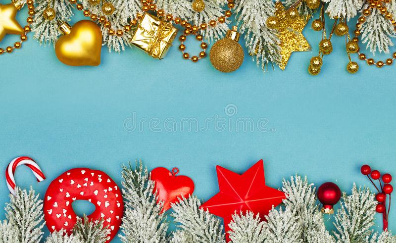Christmas border. Blue Xmas background with red holly berries, gold garland, winter holiday decor and green fir branch.  royalty free stock photos