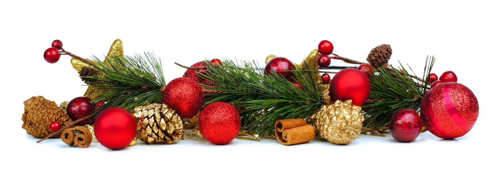 Christmas border of branches and baubles. Christmas border of branches, pine cones and red baubles over a white background stock photo