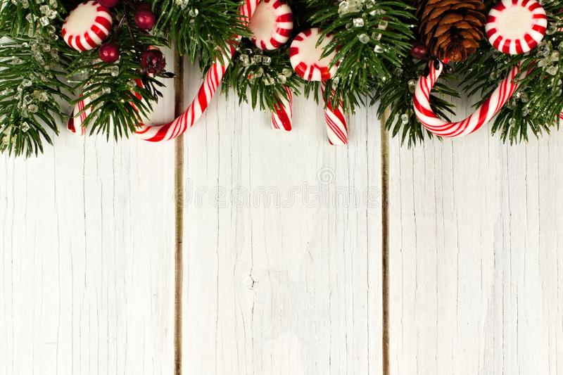 Christmas border of branches and candy canes on white wood. Christmas top border of branches and candy canes against a white wood background royalty free stock photography