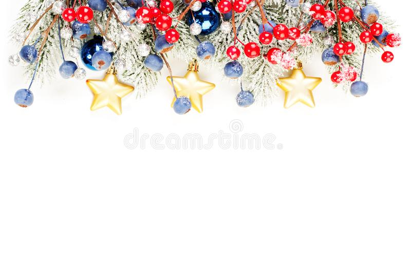 Christmas border composition. Colorful winter border with green Xmas tree twig, red holly berries and gold decoration isolated. On white background royalty free stock photos