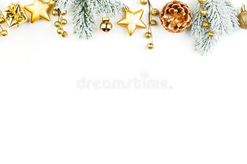 Christmas border composition. Gold decorations and green fir branch on white background. Xmas flat lay top view stock images