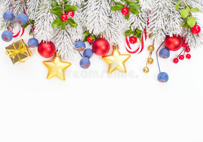 Christmas border composition with holly berries, red baubles, golden garland and green Xmas tree twig isolated on white background.  royalty free stock photos