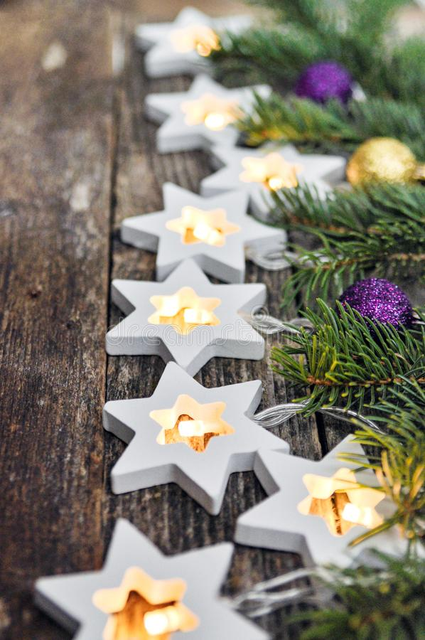Christmas Border: cozy warm lights garland stars and fir branches on rustic wooden background. top view. over hand royalty free stock photography
