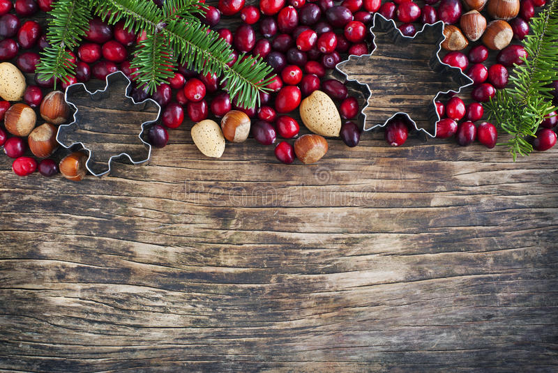 Christmas border with cranberries, spruce branch and cookie cutter. On wooden background royalty free stock photo