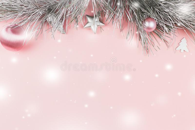 Christmas border with fir branches, christmas balls and silver ornaments on pastel pink background, snow falling royalty free stock photography
