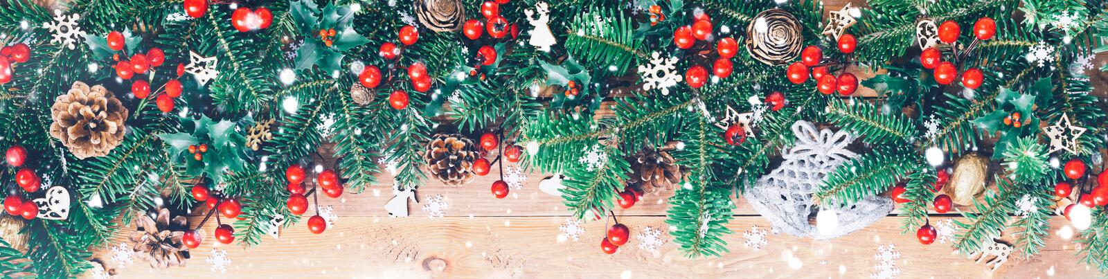 Christmas border with fir branches, red holly berries, cones and snowflakes on wooden background.  stock photos