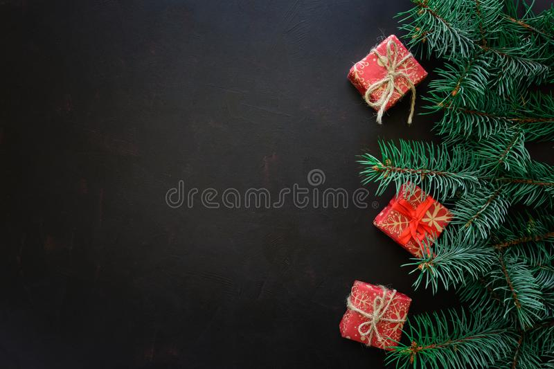 Christmas Border. Fir tree branches with gift boxes on dark wooden background. royalty free stock image