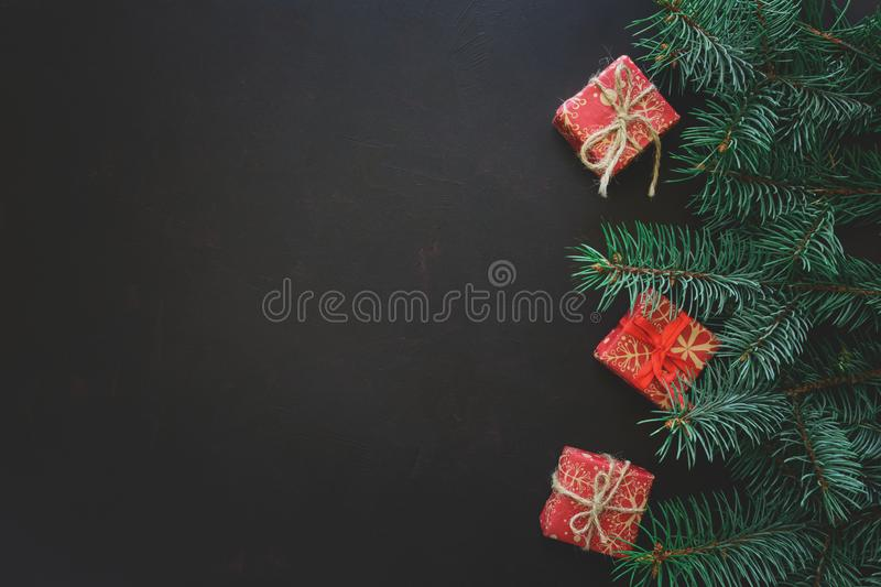 Christmas Border. Fir tree branches with gift boxes on dark wooden background. Top view. Copy space. Toned royalty free stock images
