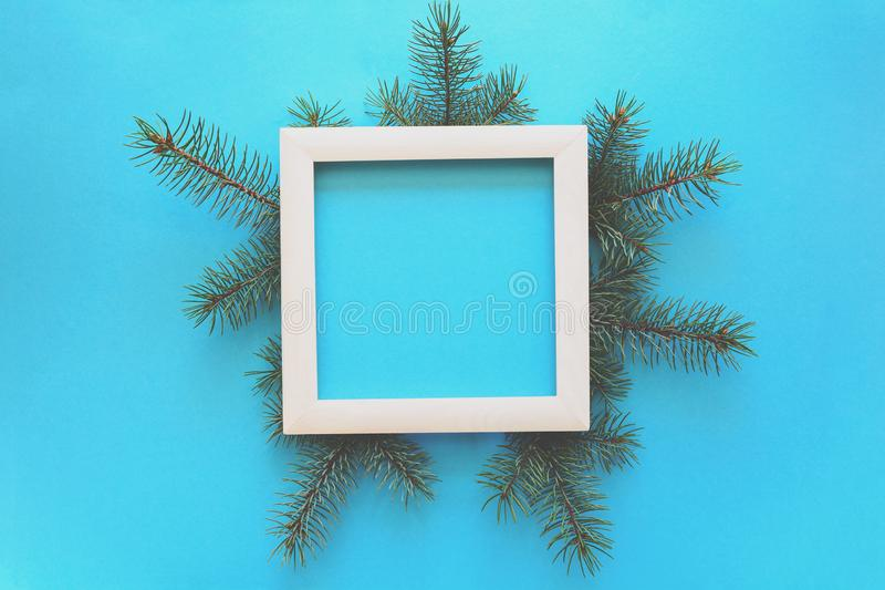 Christmas Border. Fir tree branches and white wooden frame on blue paper background. Top view. Copy space. royalty free stock image
