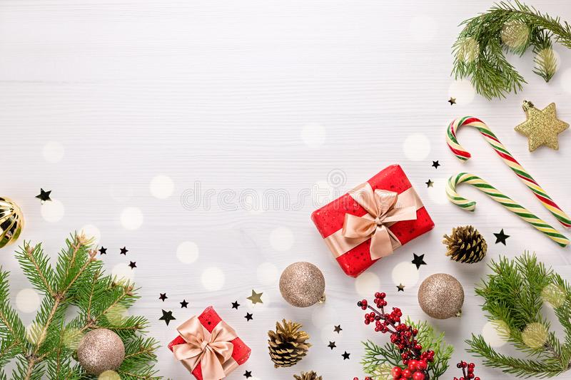 Christmas border flat lay with pine, presents, golden elements, candy canes, confetti. Christmas template on light wood stock photos