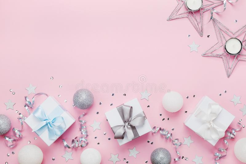 Christmas border with gift boxes, balls, decoration and sequins on pink table top view. Flat lay. Copy space for greeting card. Christmas border with gift boxes royalty free stock photo