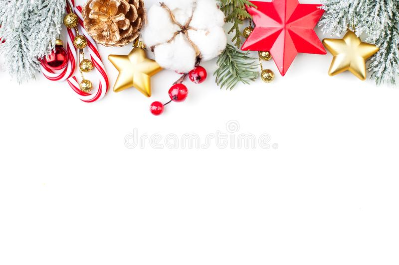 Christmas border of gold decor, green branches, red holly berries and baubles isolated on white background. Xmas and New Year. Concept. Flat lay, top view with stock photography