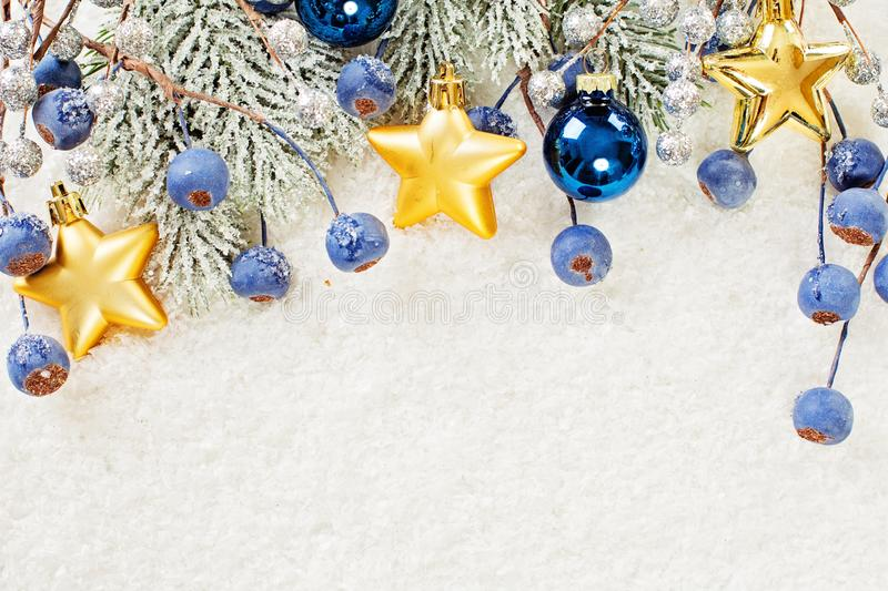 Christmas border of gold star decor, green fir branch, blue berries and baubles on winter white snow background. Xmas and New Year. Concept. Flat lay, top view royalty free stock photos