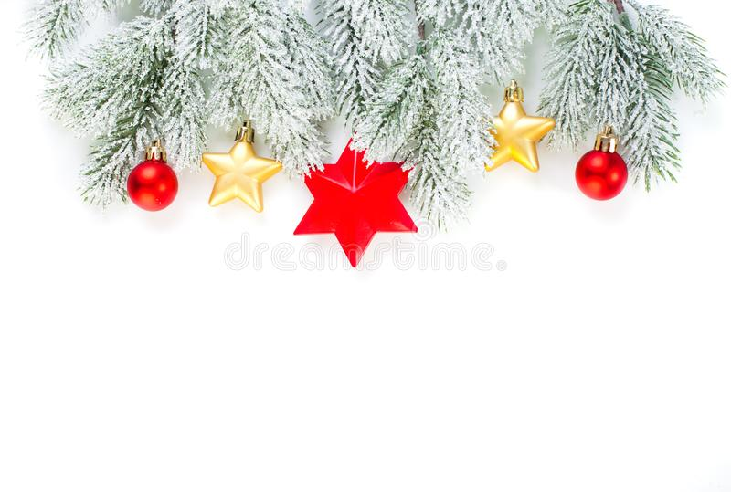 Christmas border. Green Xmas fir branch, gold stars and red glass baubles isolated on white background. Christmas decoration.  royalty free stock photo