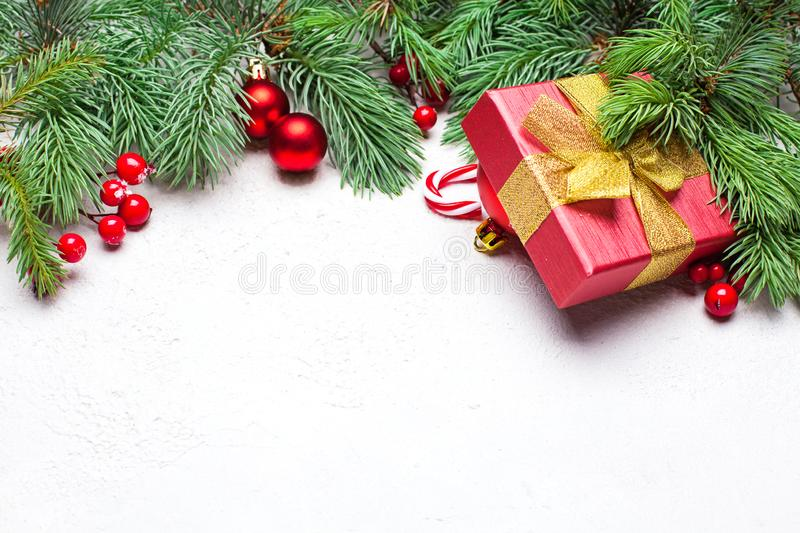 Christmas border. Green Xmas fir branch, red holly berries, gift, candy and baubles. Christmas composition, top view flat lay. With copy space on white stucco stock photography
